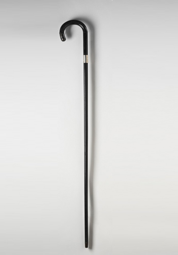 Ebony walking stick with a curved top, a small silver metallic band and a metal cap at both ends.