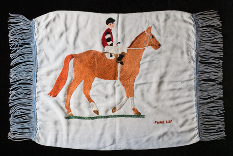 A cushion cover with an embroidered image of a horse and rider at the centre. 'Phar Lap' is stitched in red in the bottom right.