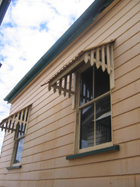Side view of shaded, glass windows on a wooden house.
