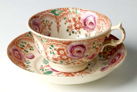 Tea cup and saucer decorated with red and pink flowers.