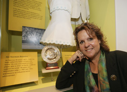 Evonne Goolagong Cawley sits beside a case containing a small circular trophy, white tennis dress, text panels and black and white photograph.