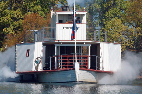 Paddle steamer on Lake Burley Griffin. A man stands in the 'ENTERPRISE' wheelhouse on the upper level. Steam can be seen coming from both sides of the lower deck of the white wooden vessel.