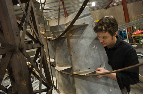 A man peers around a piece of galvanised steel, moving it into position on a large metal frame.