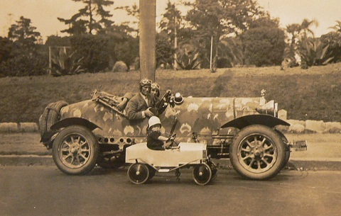 Black and white photo showing a side view of two men wearing leather flying style caps and goggles, sitting in an open-topped car which has small maps of Australia painted on the chassis. Beside them is a small child sitting in an open-topped toy car.