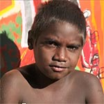 Aboriginal boy in front of a painting