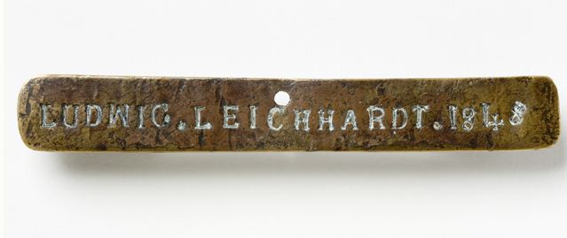 Narrow, roughly rectangular-shaped metal plate with a pitted surface, small hole centre top and marked 'LUDWIG. LEICHHARDT. 1848'.