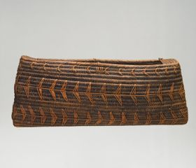 Basket made of 'alu (a native creeper with tendrils) and coconut fibres with a slightly baggy rectangular opening, in a dark brown colour.