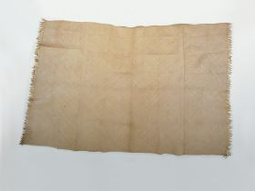 Mat made of diagonally plaited light yellow leaf strips, by alternately placing one stripe with the glazed side of the leaf up and the other with the unglazed side up.