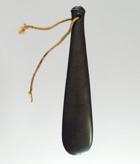 Flat club made of dark basalt, with hole drilled at the grip end with a strap made of twisted twine.
