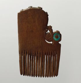 Comb made of dark brown wood, embellished with a greenish opalescent piece of shell.