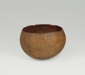 Drinking bowl made from a light-brown young coconut where the shell was split open just above its widest point.