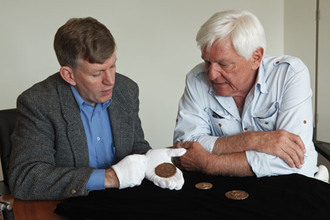 Two men, seated a table, with three circular medallions. The man on the left is wearing white gloves and holds one of the medals in the palm of his left hand.