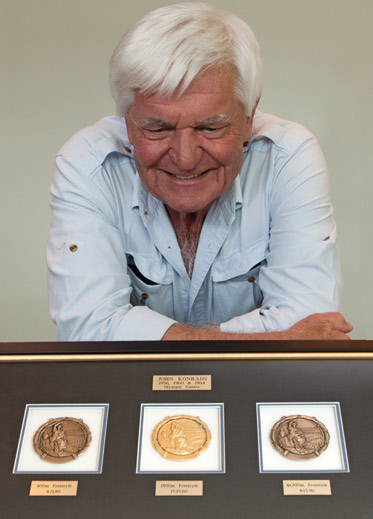 Colour photograph of a man resting with folded arms on a table. In front is a framed set of three circular medals.