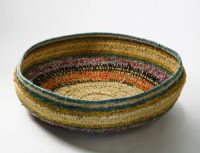 A large shallow basket made of bands of grasses which have been bound in plant material dyed in different colours and in strands of wool.