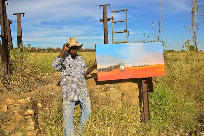 Mervyn Street holding his painting The Old Trucking Yards (2012)