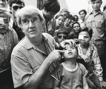 Fred Hollows points to the left eye of a young boy at a busy clinic in Vietnam.