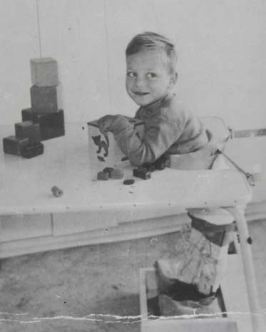 Black and white photo of a young boy at a table. He wears callipers on his legs and is playing with a box and blocks.