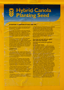 Conditions of sale and use label on Pacific Seeds 'Hybrid Canola Planting Seed' bucket.