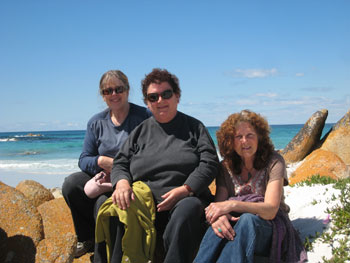 Three women sitting on rocks with the ocean in the background.