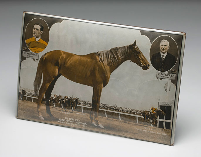 Tin plaque showing side view of a racehorse with the text underneath: 'PETER PAN, PANTHEON-ALWINA, WNNER MELBOURNE CUP, 1930'. Portraits of two men are inset, top left 'D MUNRO, RIDER' and top right 'F McGRATH, TRAINER'.
