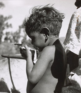 A black and white photograph that depicts an Aboriginal boy sitting in a canoe eating a piece of watermelon.
