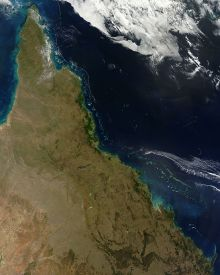Distance aerial photograph showing the coastline of Queensland, ocean offshore and clouds to the north.