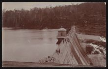A sepia photo taken from above a concrete dam wall. Several people stand on the wall, looking at the water on one side, and the spillway on the other.