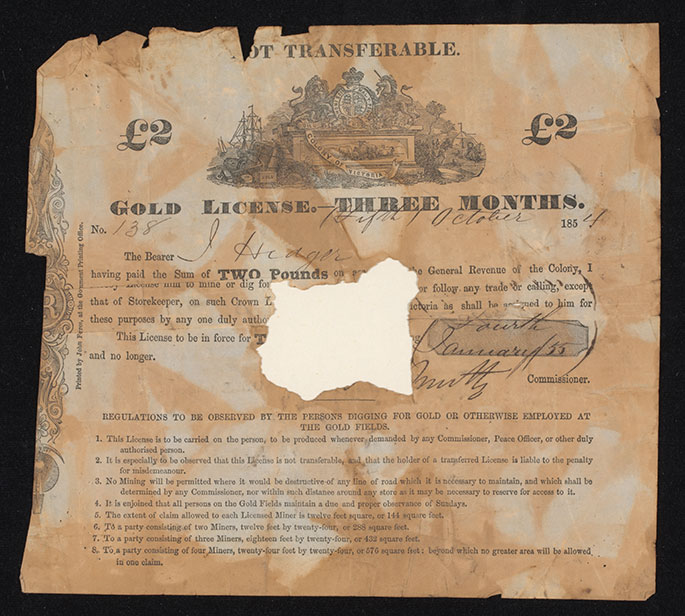 Photograph of a 'GOLD LICENSE' printed on paper, which has been folded and torn around the edges and has a section missing at the centre. A 'Colony of Victoria' coat of arms is centre top, wth printed and handwritten text underneath.
