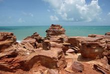 Colour photographs showing reddish rock formations overlooking the ocean.