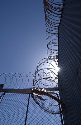 Photo looking into the sun at the top of a gate with barbed wire on top