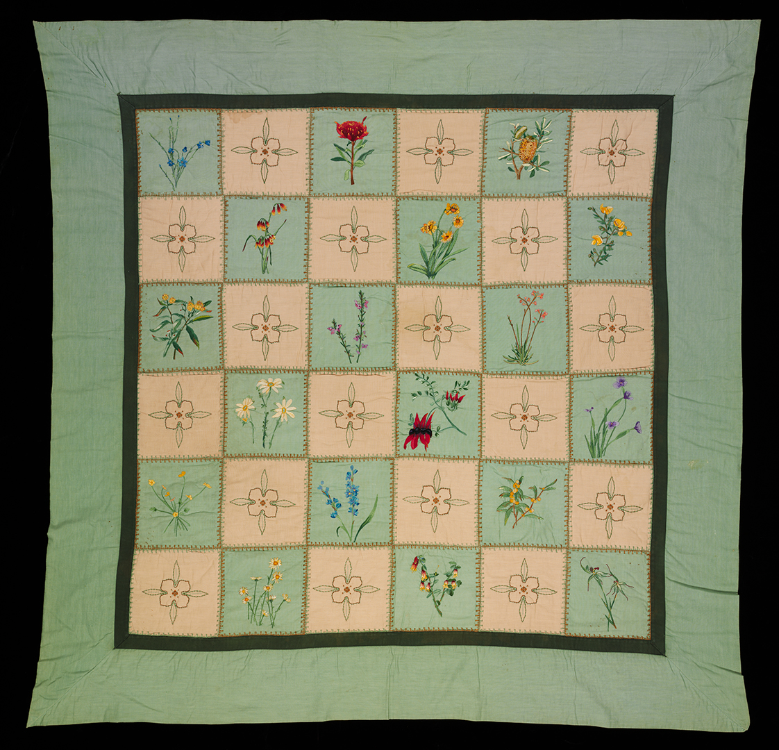 Fabric quilt with green and cream patchwork squares embroidered by hand with Australian wildflower designs, and a recurring passionfruit vine flower design.