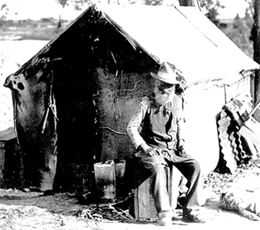 Old man seated on a crate in front of his simple dwelling with a dog at his feet.