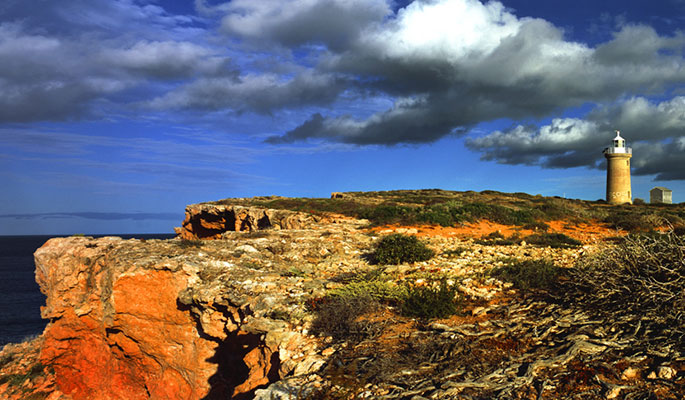 Colour photo of a piece of coastline showing cliffs of orange rock and a small lighthouse in the distance.