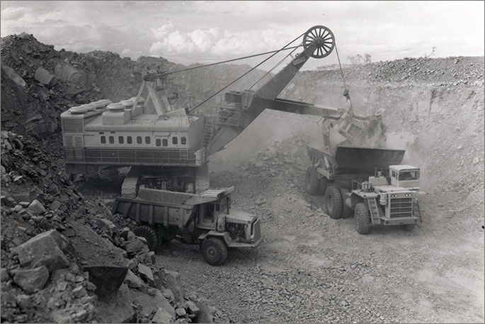Black and white photo of large power shovel dumping ore into one of two large mining trucks.
