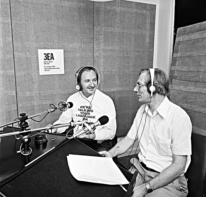 two men sitting in a radio studio in front of microphones. They are smiling and clearly in conversation. The present is wearing a top saying 'We're talking your language on 3EA'