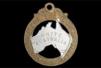 this 28mm-high badge has the words 'Australia for the Australians' stamped on the rim and the words 'White Australia' stamped on silver-painted representation of the Australian continent in the middle.