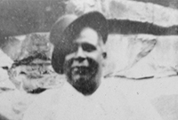 Aboriginal man, smiling, stands facing the camera, a hat set at jaunty angle on his head.