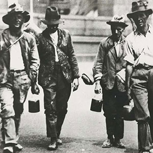 Four men walking towards the camera dressed in shabby clothes. Most are carrying swags and bill cans