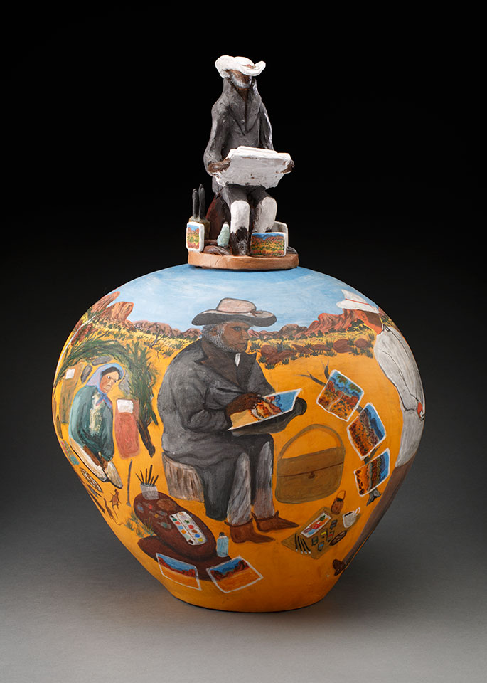 A bulbous pot painted in bright colours, showing a view of an Aboriginal artists at work in the desert. The pot's lid is a sculpted figure of a seated artist.