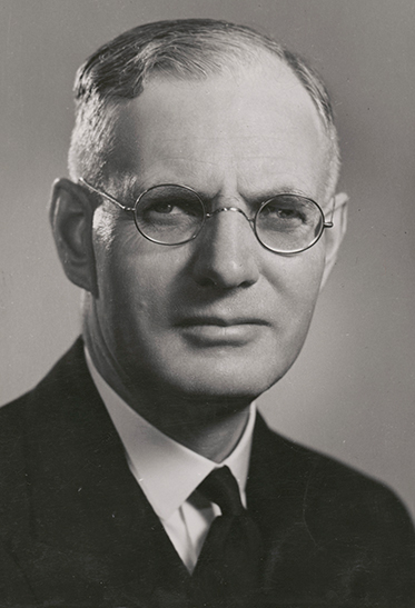 studio black and white photo of Curtin.  He is wearing a dark suit and glasses
