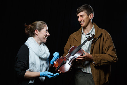 Woman and man inspecting a violin