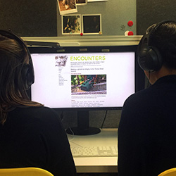 Two people with headphones watching a computer screen