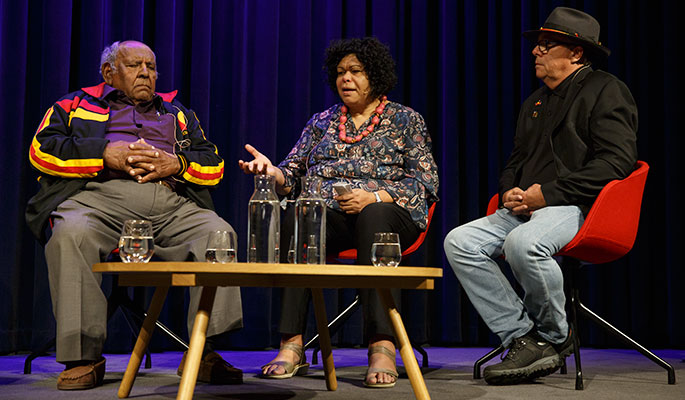 Two men and one woman sitting on a stage in discussion