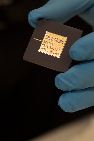 a hand wearing plastic glove holds coin-sized black square with gold-coloured chip at its centre
