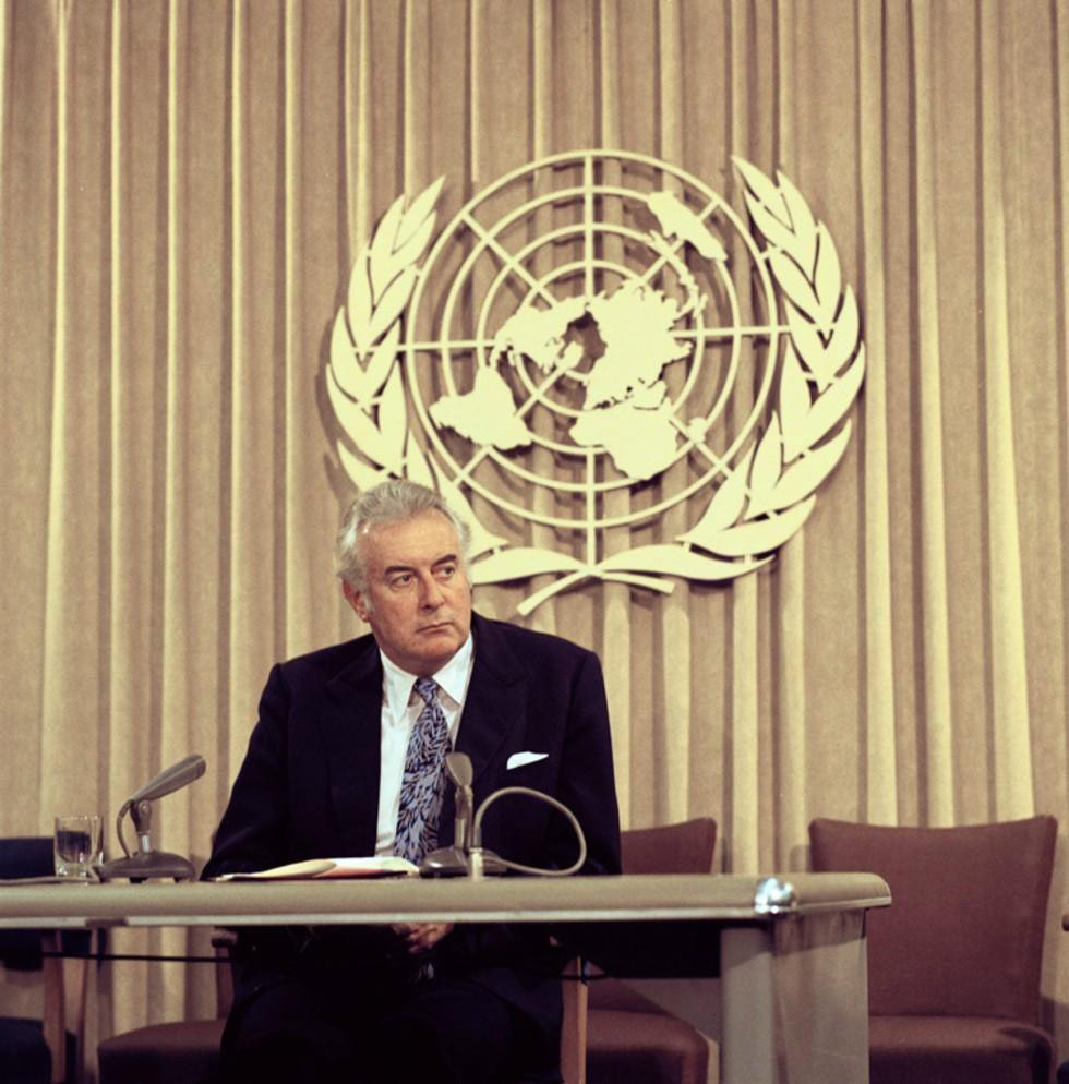 Colour photo of middle-aged man in suit sitting behind desk with UN symbol in background. - click to view larger image