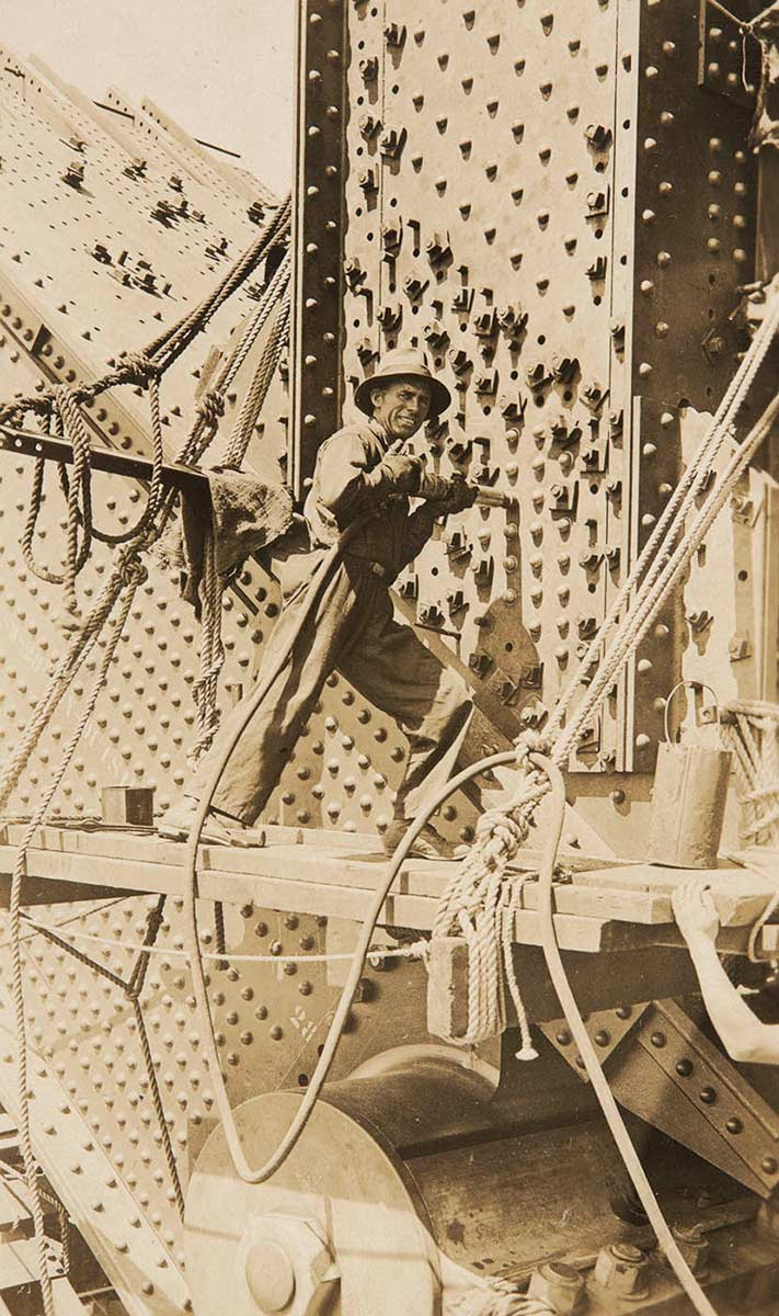 A man stands on a plank, which is attached to the bridge by ropes. He is holding a rivet gun against the metalwork, which is covered in rivets. - click to view larger image