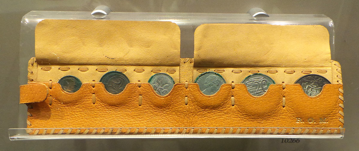A yellow leather pouch containing six tarnished coins – the one, two, five, 10, 20 and 50-cent pieces. The initials R G M are embossed in gold.