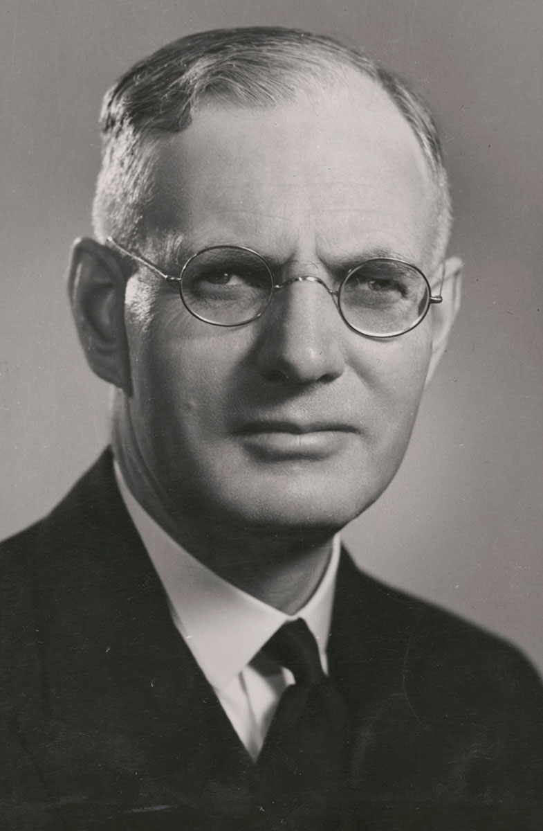 Studio black and white photo of Curtin. He is wearing a dark suit and glasses. - click to view larger image
