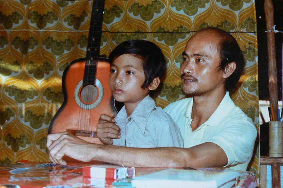 A man sits at a table with a young boy on his lap. Behind them a guitar is visible. - click to view larger image