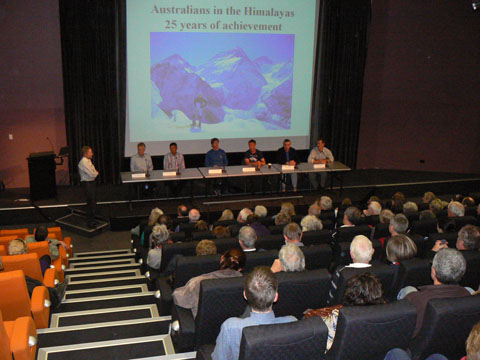 Public seminar with six men seated on a stage. An image of a man standing in front of snow-covered mountains is projected at the rear. A crowd of people is seated in front of the men.
